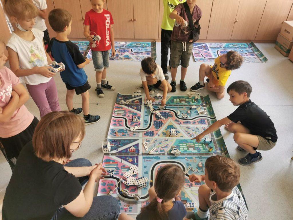 Grupa dzieci zgromadzona wokół planszy przedstawiającej ulice miasteczka.