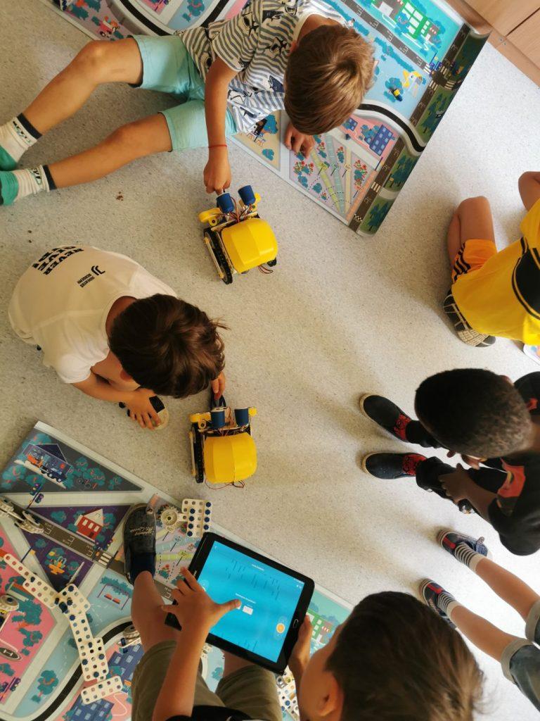 Dzieci oglądaja roboty. Chłopiec z tabletem w rękach poznaje możliwości aplikacji do sterowania robotami.