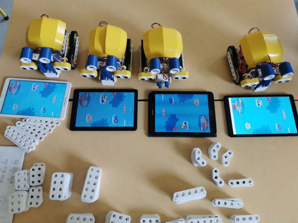 Widok kilku zestawów edukacyjnych SkriKit+. Na podłodze leżą roboty, tablety z aplikacjami do sterowania robotami oraz elementy służące do budowy robotów.