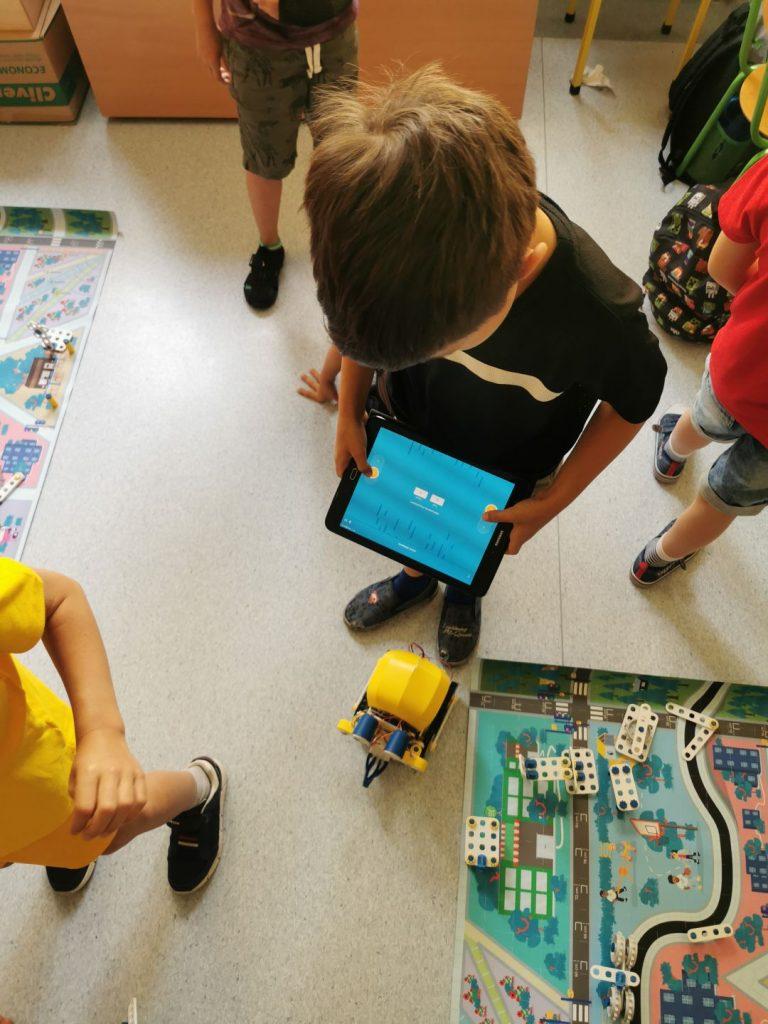 Chłopiec testuje swojego robota. Steruje nim za pomocą aplikacji na tablecie.