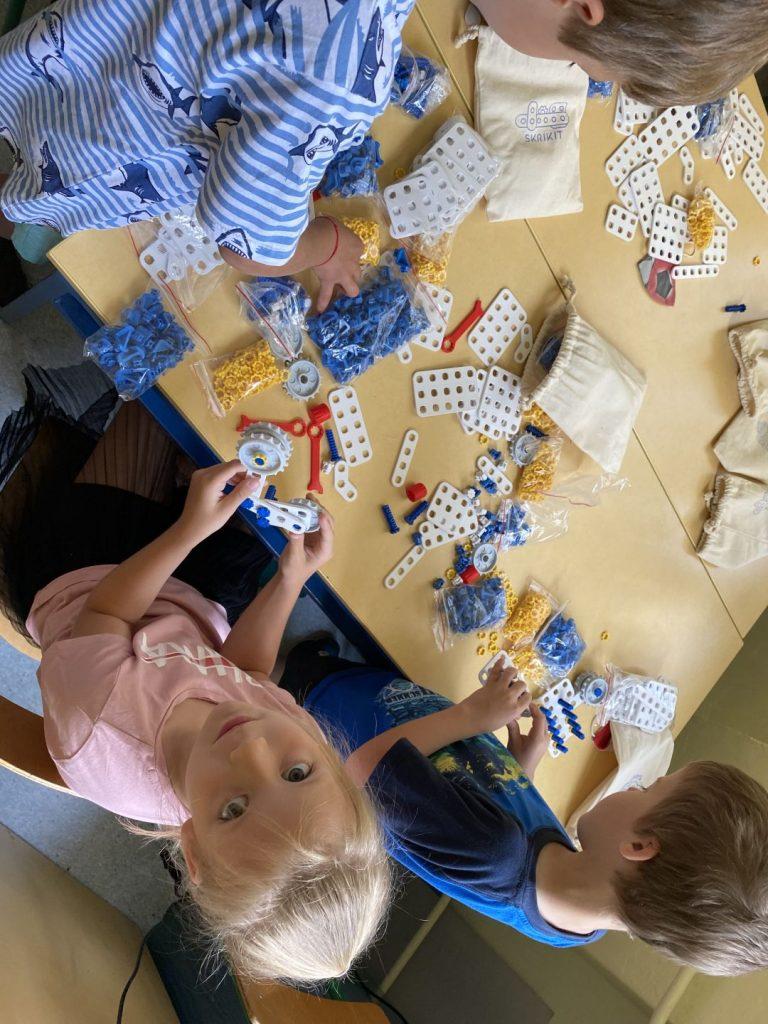 Dzieci składają roboty z gotowych elementów.