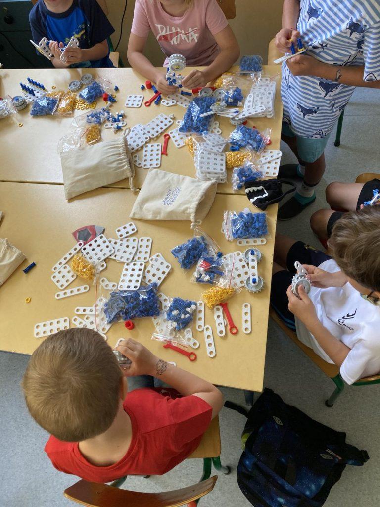 Grupa dzieci siedzących przy stole i budujących swoje roboty