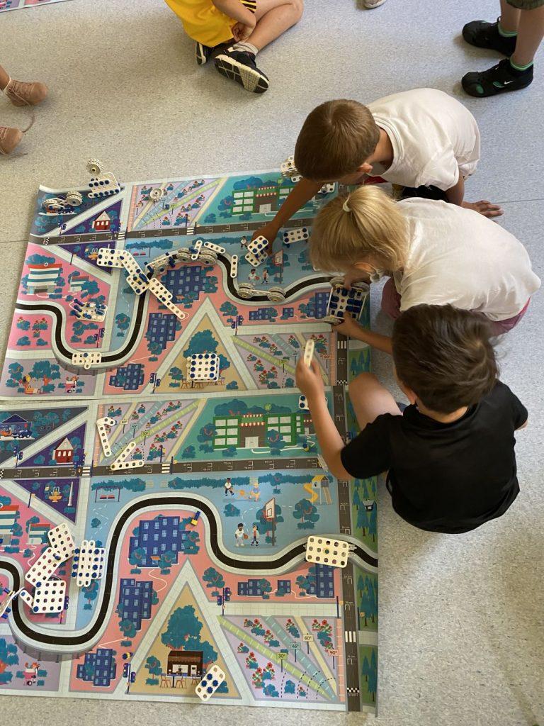 Dzieci zgromadzone wokół planszy przedstaawiającej wirtualne miasto